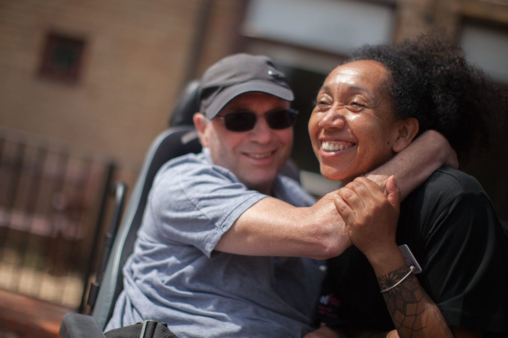 A man is hugging his carer outside a brick building
