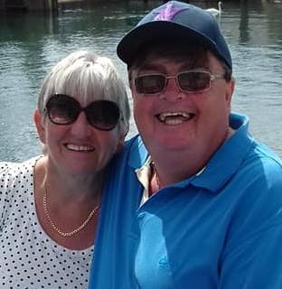 Norrms and his wife stand smiling at the camera wearing sunglasses in front of a large body of water