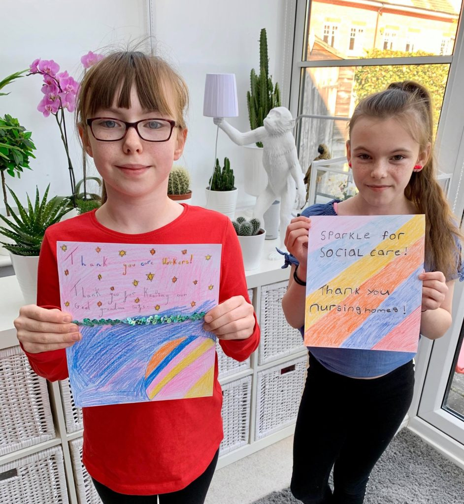 Photo of 2 girls showing their colouring for #SparkleforSocialCare