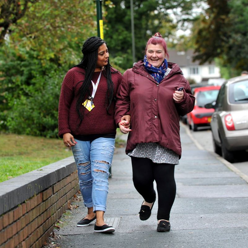 Photo of carer and individual walking down street
