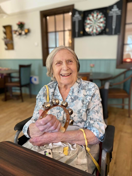 Older lady is sat at a table in a care home day room, holding a small hand instrument with bells, smiling at the camera.